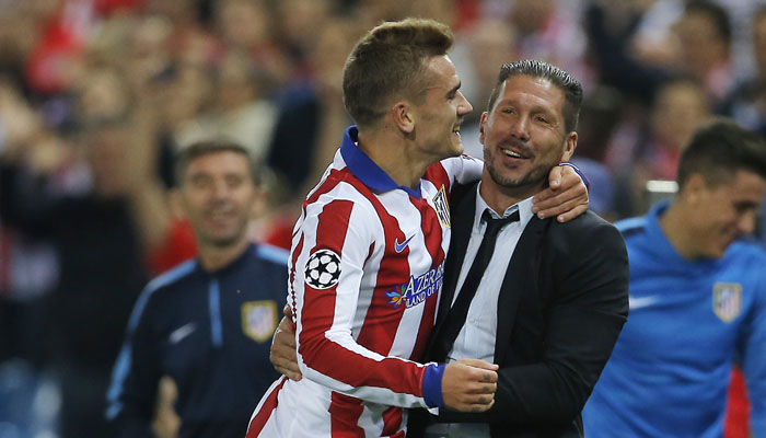 Atletico's Antoine Griezmann, left, celebrates with his coach Diego Simeone after scoring during the Group A Champions League soccer match between Atletico de Madrid and Malmo at the Vicente Calderon stadium in Madrid, Spain, Wednesday, Oct. 22, 2014. (AP Photo/Andres Kudacki)
