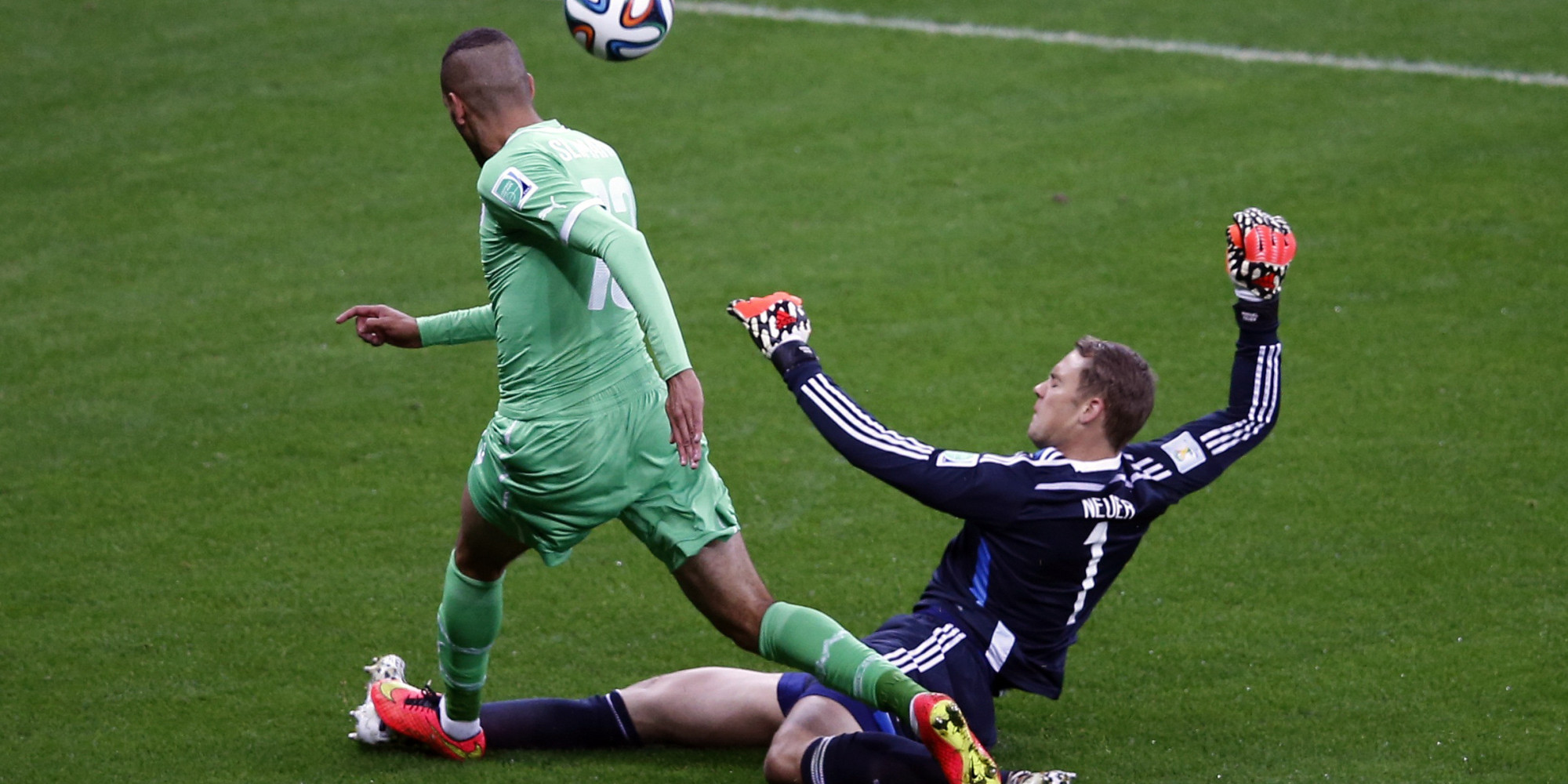 Germany's goalkeeper Neuer challenges Algeria's Slimani during their 2014 World Cup round of 16 game at the Beira Rio stadium in Porto Alegre